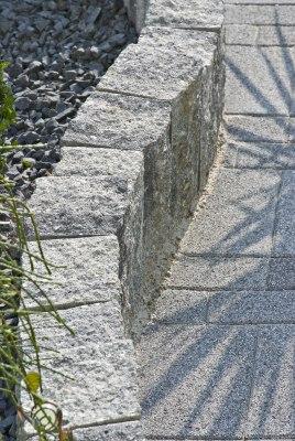 Gepflasterte Beeteinfassung mit grau-schwarz nuanciert Steinmauer mit gepflasterter Einfahrt und schwarzen Kieselsteinen