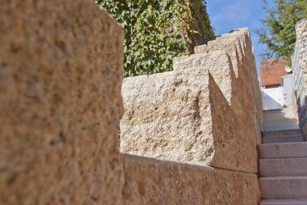 Steinmauer aus beigem Sandstein mit gepflasterter Treppe und weißer Gartentuere und weißes Haus und Mauer mit Efeu und Steinmauer und Himmel