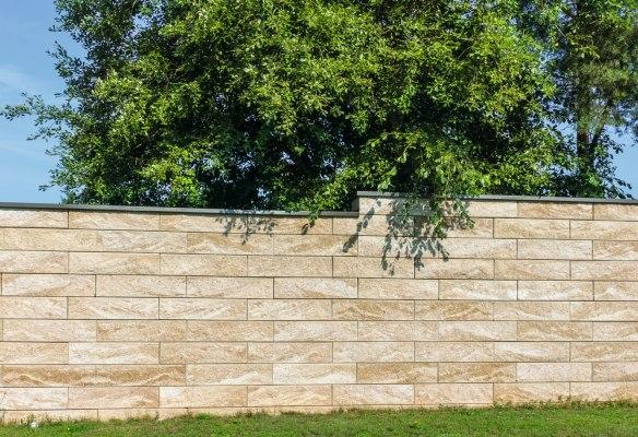 Gepflasterte Steinmauer im Reihenmauerwerk aus beigem Sandstein und Baum und Wiese und Schattenwurf und Himmel
