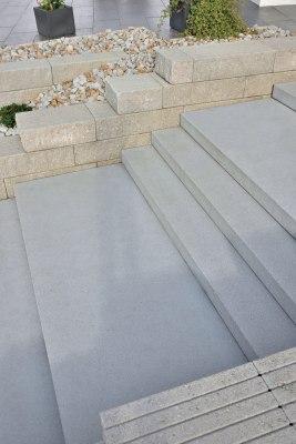Grauer Blockstufe aus selbstverdichtendem Hochleistungsbeton und Steinmauer in grau