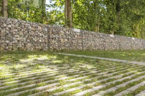 Graue Rasenliner aus Rasenplatten mit Gras in den Zwischenraeumen und Steinwand aus Kieselsteinen und Baeumen