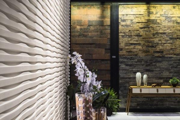 Wandverkleidung in hellgrau und wellenfoermig und Sideboard mit Holzauflage und Orchideen in Vase und drei weissen Vasen und Stuhl und Bild auf dem gepflasterten Steinboden
