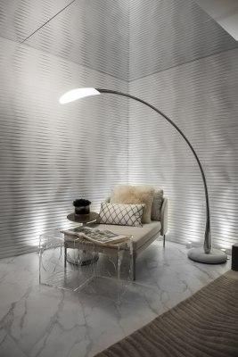 Wandverkleidung aus Sichtbeton in weiss und wellenfoermig und Glastisch mit offenem Magazin und Stehlampe und Stuhl mit Kissen und Tisch mit Dekoration