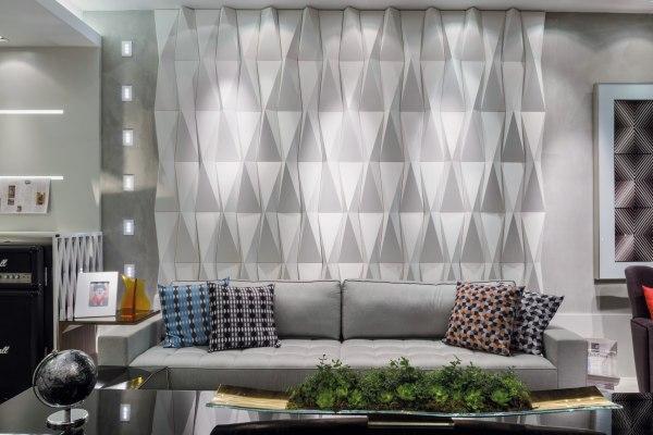 Wandverkleidung aus Wandfliesen in weiß und mit Origamimuster und Couch mit Kissen und Tisch mit Dekoration und Glasvase und Globus und Tisch mit Bild und Vase