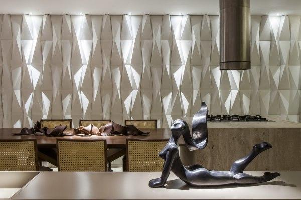 Wandverkleidung aus Wandfliesen in weiss mit Origamimuster und Tisch in Holzoptik mit Dekoration und Stuehlen und Tisch mit Figur und Feuerstelle und Abzug