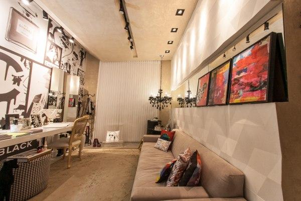 Wandverkleidung aus Wandfliesen aus Sichtbeton mit Origamimuster und Couch mit bunten Kissen und bunten Bildern auf Wandfliese und Tisch mit Magazinen und Stuhl und Bilder in schwarz-weiss an den Waeden und weissen Vorhaengen und Kronleuchter