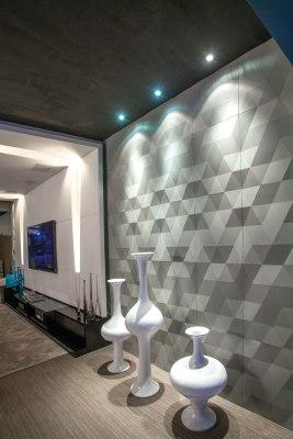 Wandverkleidung Rautenfoermig in verschiedenen Gruentoenen und Stuhl und Tisch mit Dekoration und Lampen