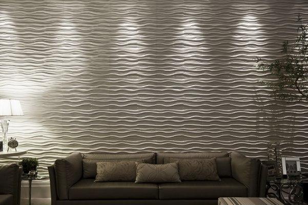 Wandverkleidung mit Wandfliesen aus Sichtbeton und wellenfoermig und Couch mit Kissen und Tisch mit Dekoration und Stehlampe