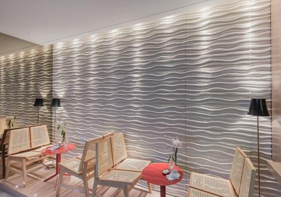 Wandverkleidung aus hellgrauem Sichtbeton mit Wellenform und orangen Tischen und Blumenvasen mit Blumen und Kaffeetasse und Zucker und hellen Stuehlen und Stehlampen