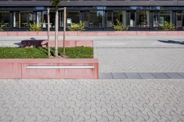 Hellgrau gepflasterter Parkplatz mit Pflastersteinen in dynamischer Optik und dunkelgrauer Parkabgrenzung und roten Sitzbaenken aus Stein und Wiese und Baum und Terrasse und Stuehle und Tische und Fenster