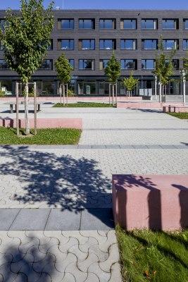 Hellgrau gepflasterter Parkplatz mit Pflastersteinen in dynamischer Optik und dunkelgrauer Parkabgrenzung und roter Sitzbank us Stein und Wiese und Baum und Fenster und Stuehle und Tische und Schattenwurf