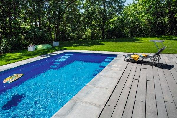 Grau gepflasterte Terrasse in anthrazit gekalkt und Pool mit Pololeinfassung aus Anthrazit farbigem Sichtbeton und Sonnenstuhl mit Handtuch und Magazin und Surfbrett in Pool und Wiese und Sitzsack und weißem Tisch
