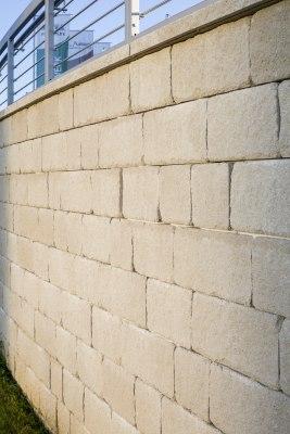 Gepflasterte Steinmauer aus Kalkstein mit Antikoptik mit Edelstahlgelaender und Fahnen und Himmel
