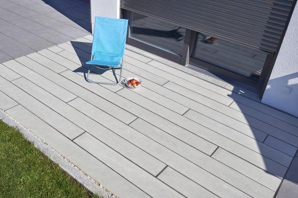 Gepflasterter Terrassenboden aus grau gekalktem Beton mit Holzoptik vor weißem Haus mit dunklen Tuerrahmen und halbgeschlossenem Rolladen und hellblauer Liegestuhl mit weißer Obstschale und Aepfeln und Wiese und weißen Kieselsteinen und Schattenwurf