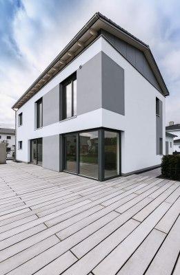 Grau gepflasterte Terrasse vor weißem Haus mit grauer Farbe mit dunklen Tuerrahmen und Glasfasanen und großen Terrassentueren und Himmel und Hecke