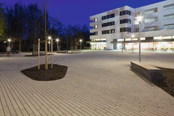 Vorplatz mit laenglichen grauen Steinplatten und Sitzgelegenheit und Baum und weißes Haus und beleuchtete Geschaefte