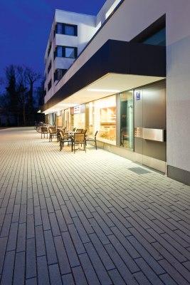 Vorplatz mit laenglichen grauen Steinplatten und Baum und weißes Haus und beleuchtete Geschaefte