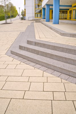 Vorplatz aus laenglichen beigen Steinplatten mit grauen Stufen aus Beton und Steinplatten vor Gebaeude mit Glasfront