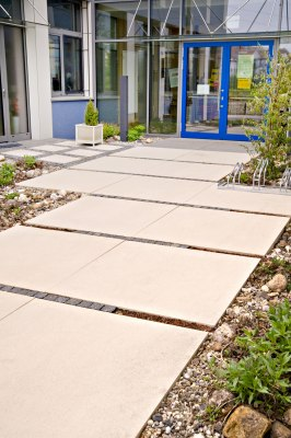 Hauseingang aus grossen quadratischen beigen Steinplatten mit Kies umrandet und Gebaeude mit Glasfront