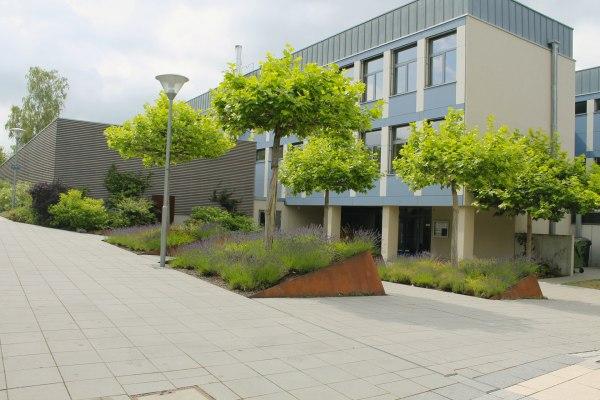 Vorplatz aus grauen quadratischen Steinplatten und Baeume und Gebaeude mit Fenstern und bepflanztem Hochbeet und Laterne und Himmel