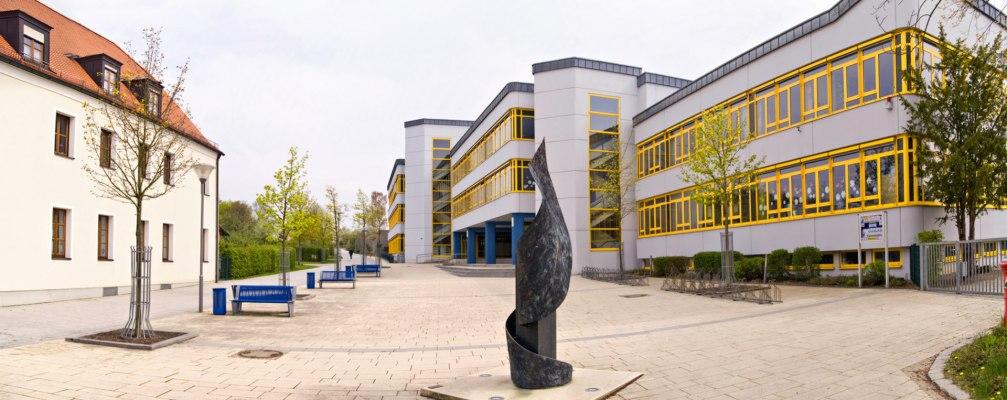 Schulhof und Vorplatz aus beigen und sandsteinfarbenen Steinplatten und Schule mit gelben Fenstern und schwarzer Skulptur und Baeume und blaue Sitzbaenke und beiges Haus und Himmel