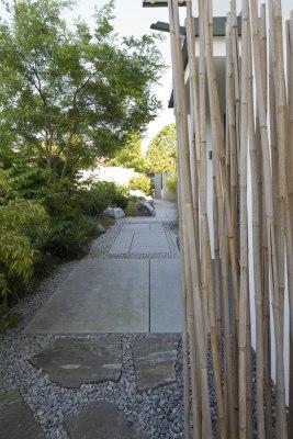 Gartenweg aus grossen laenglichen hellgrauen Steinplatten aus Beton von Kieselsteinen umrandet und grosse Steinfelsen und Bambus an den Wegraendern