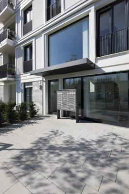 steinboden aus grauen Steinen aus Beton und Eingang von Mehrfamilienhaus aus Glas