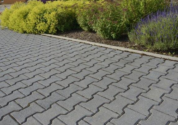 Gepflasterte Hofeinfahrt in grau aus Beton mit bepflanztem Beet und Pflanzen und Blumen und Straße