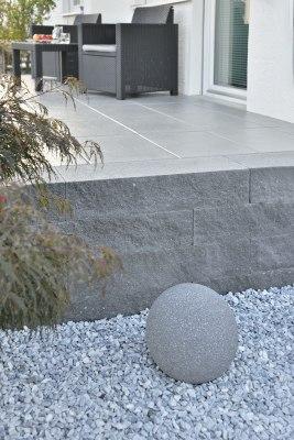 Gepflasterte Terrasse und Steinmauer in Schieferoptik und Kieselbeet und großem Stein und Stuehlen und Tisch und Obstteller und Aepfel und Balkontuer und Pflanzen