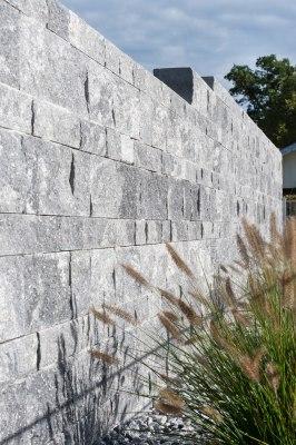 Gepflasterte Steinmauer in grau schwarz im Schichtenmauerwerk mit grauen Kieselsteinen und Graesern und Himmel und Baeumen