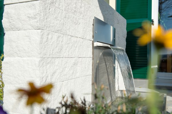 Steinmauer aus Kreide mit Wasserwand mit Wasserfall und Blumen und Glastuer