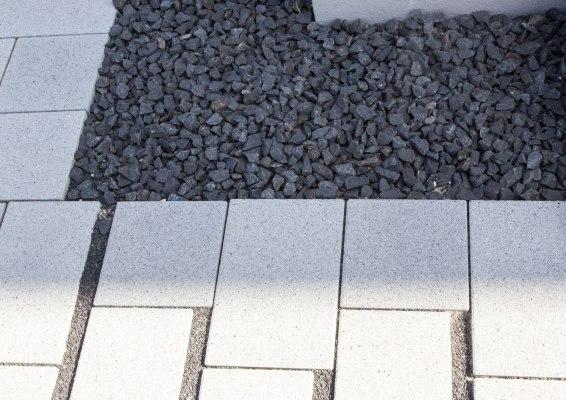 Hellgrau gepflasterte Terrasse und Einfahrt und Hinterhof mit dunklen Rasenlinern mit Kieselsteinen und Basalt Splitt in den Zwischenraeumen