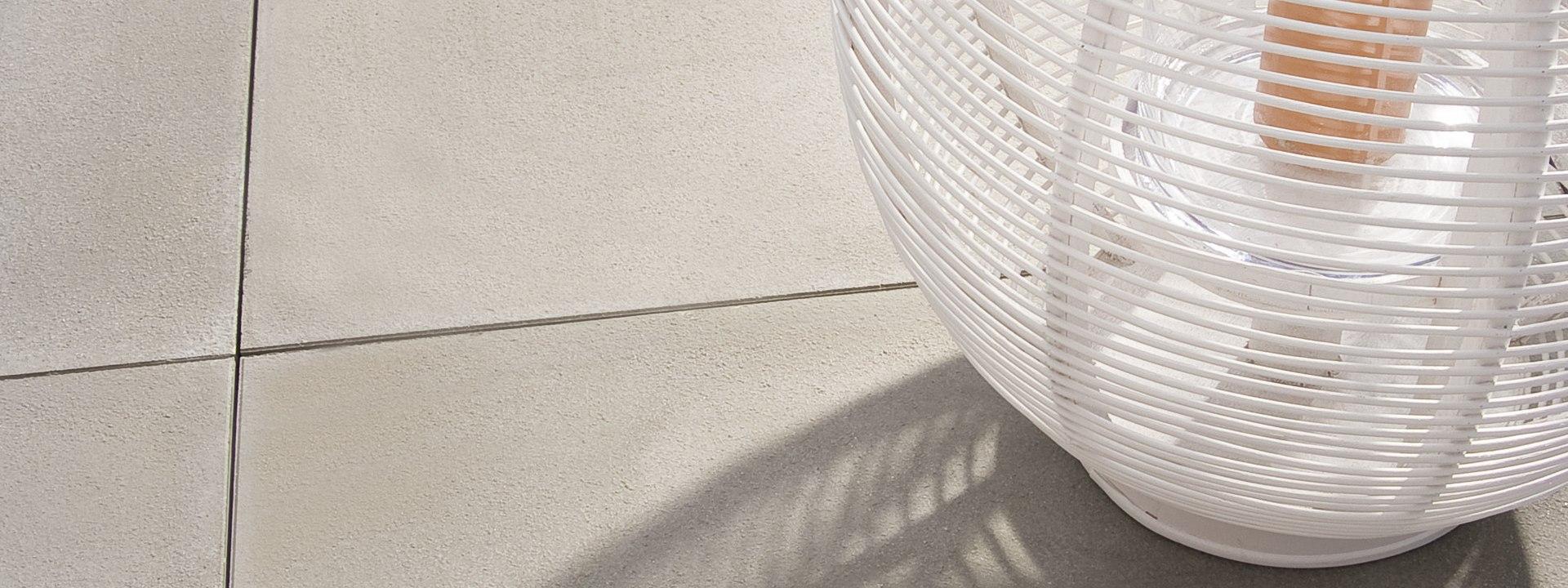 Terrassenplatte GARTENPLATTE von GODELMANN. Grauer gepflasterter Steinboden mit oranger Kerze und Dekoration