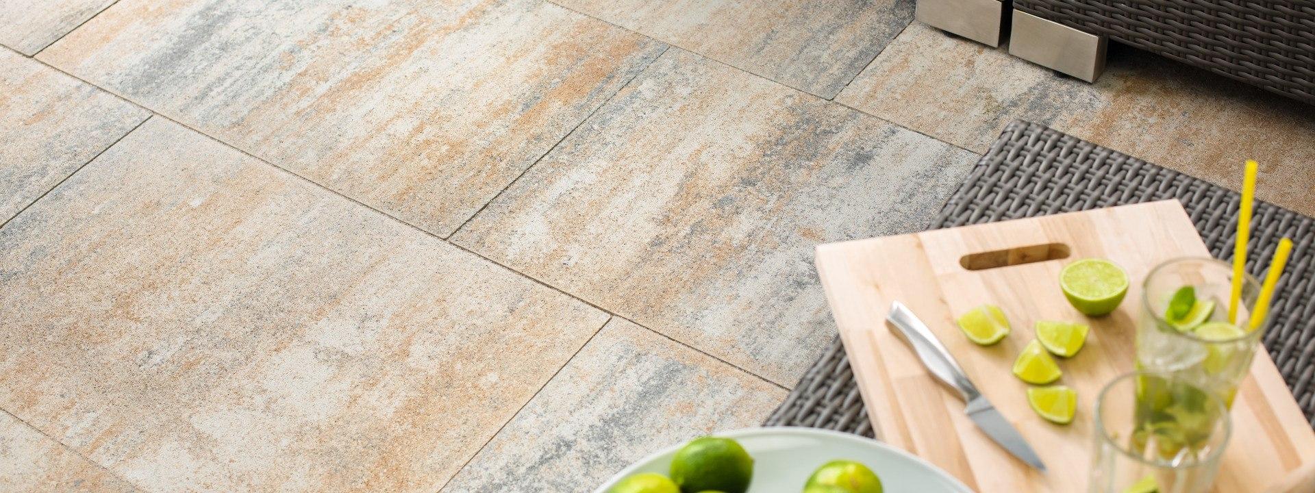 Gepflasterter Steinboden in Muschelkalk Optik und Tisch mit aufgeschnittenen Limetten und Messer und Gläsern mit Limetten und Strohhalm