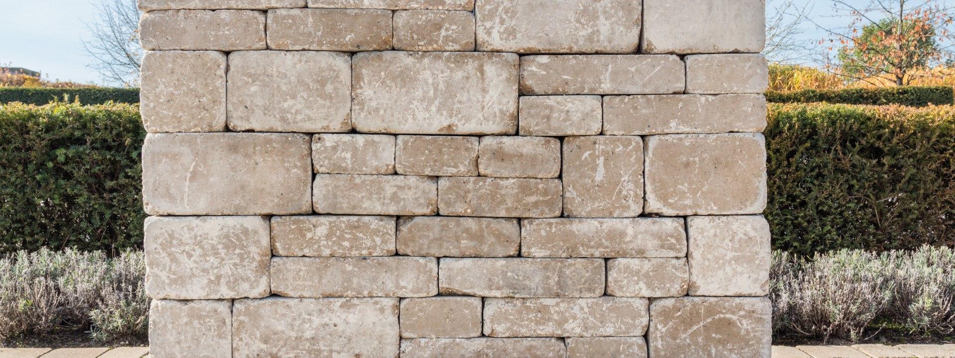 Gepflasterte Steinmauer aus Sandstein und Hecke und bepflanztes Beet und Baeume und Hecken