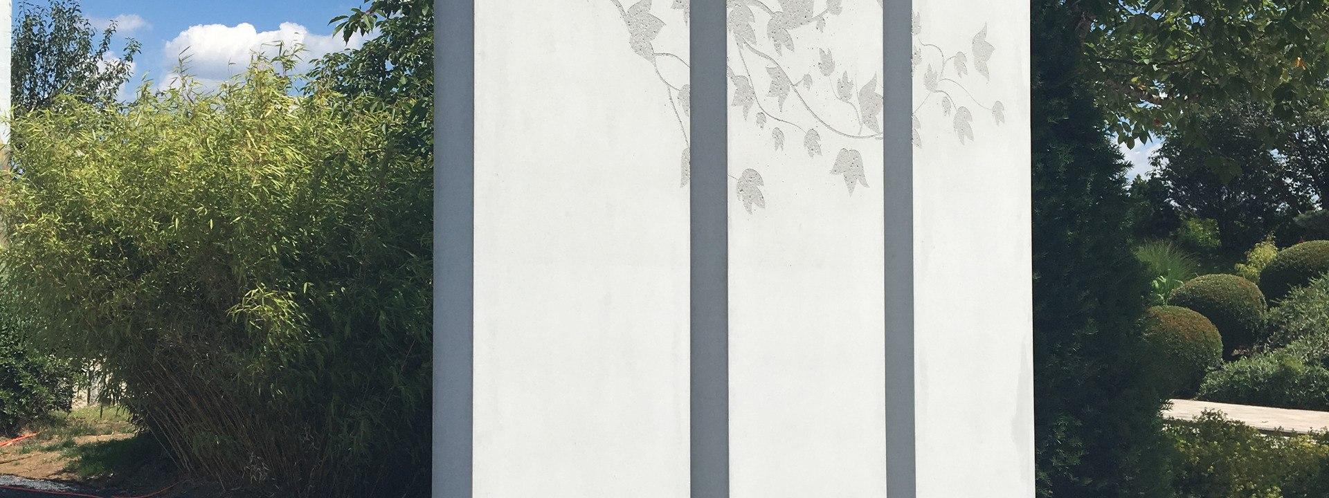 Massimo Stele Raumteiler aus grauem Sichtbeton mit bestrahlter Blumenintarsie und Zweigen und Blaettern und Voegeln