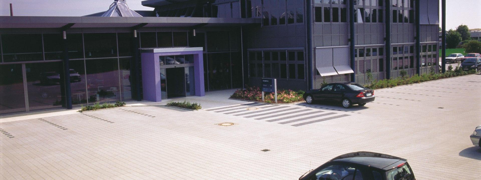 Pflasterstein GOWITEC von GODELMANN. Gepflasterte Parklplaetze und Einfahrt vor Gebauede mit geparkten Autos und bepflanzten Rindenmulchbeeten und Jealosie und lila gestrichener Eingang