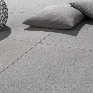 Gepflasterte Terrasse aus Terrassenplatten mit Großformatplatten in 100x100 aus Sichtbeton mit grauen Kissen und Bastkoerben und Schattenwurf