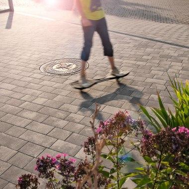 Gepflasterte Hofeinfahrt rollgeraeuscharm in grau schwarz im Klein- und Grosspflastersystem mit bepflanztem Blumenbeet und Hoverboard mit Kind und Gullideckel