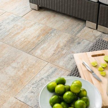 Terrassenplatte von GODELMANN. Gepflasterter Steinboden in Muschelkalk Optik und Tisch mit aufgeschnittenen Limetten und Messer und Gläsern mit Limetten und Strohhalm