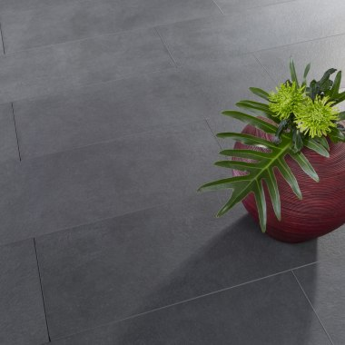 Gepflasterter Steinboden in anthrazit aus großformatigen Beton Feinsteinzeugplatten 120x40 cm Chianto mit bepflanzter roter Vase