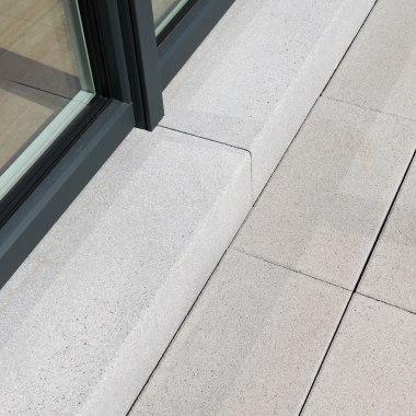Blockstufe Treppenstufe Gepflasterter Terrasseneingang in ferro grau uni schwarzer Türrahmen und gepflasterter Steinboden in hellgrau
