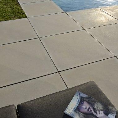 Gepflasterte Poolumrahmung Massimo light aus Großformatpflaster 100x100 aus Sichtbeton Platten mit Wiese und Tisch und Sessel und
