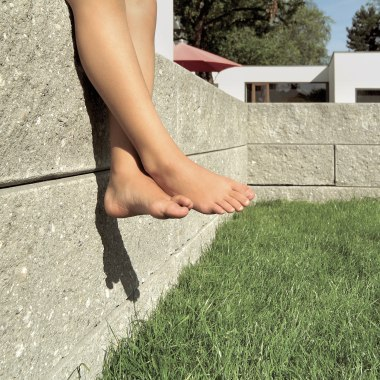 Gartenmauerstein GRANBLOCK von GODELMANN. Graue gepflasterte Steinmauer in großformatigem Mauer und Stützwandsystem mit bruchrauen Sichtflaechen und gruene Wiese udn Kinderfuesse und Haus