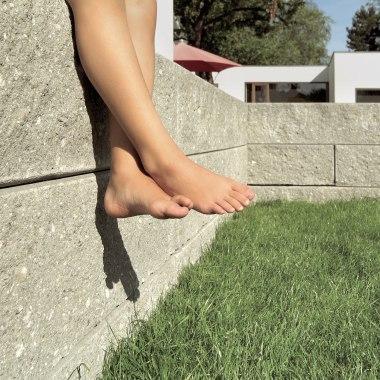 Graue gepflasterte Steinmauer in großformatigem Mauer und Stützwandsystem mit bruchrauen Sichtflaechen und gruene Wiese udn Kinderfuesse und Haus