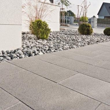 Terrassenplatte MOLINA light von GODELMANN Grau gepflasterte Terrasse aus Sichtbetonplatten mit grauen Kieselsteinen und Buchsbaeumen und weiße Hauswand