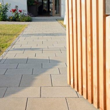 Gepflasterter Hauseingang und Eingang mit grauen Pflastersteinen und Holztüre und Wiese
