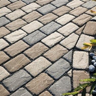 Gepflasterter Steinboden in antik Optik und in Kleinpflastersystem mit dunklen Kieselsteinen in den Zwischenraeumen und bepflanztem Kieselbeet und Aesten