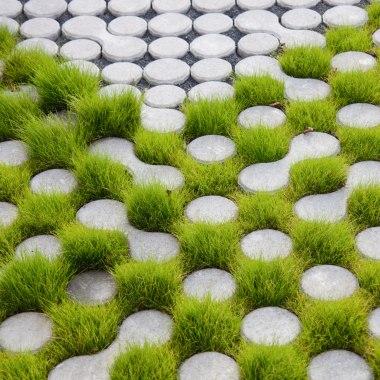 Rasenkammerstein in hellgrau mit Gras in den Zwischenraeumenals Pflasterplatte verlegt