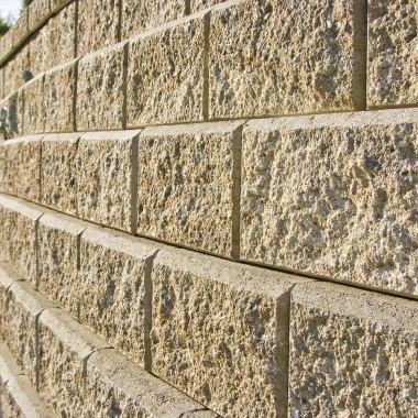 Sandsteinmauer aus Muschelkalk und bruchrau mit hoher Stuetzwand und moertellos und Geogitter bewährte Erde mit gepflasterten Steintreppen und Kieselsteinen und Hecke